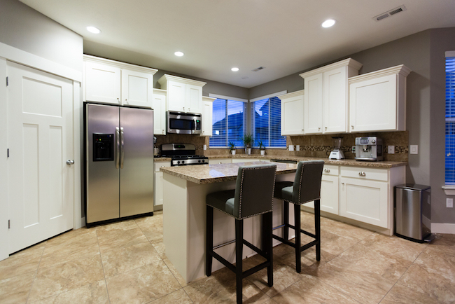 Image of white shaker cabinets in kitchen with crown molding, tile floor and quartz countertops