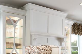 photo of a built in range hood using custom white shaker cabinets