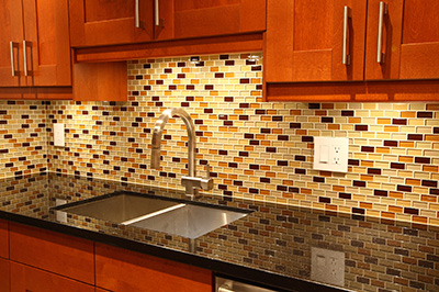 image of a kitchen with maple shaker cabinets, glass mosaic tile backsplash, and quartz counters