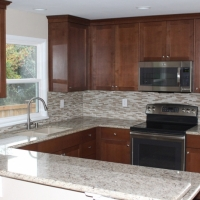 After photo showing new quartz countertops, silgranite sink, new maple cabinets, and tile backsplash